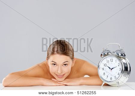 Smiling relaxed woman leaning forwards resting her arms and head on a table alongside a retro style silver alarm clock with bells