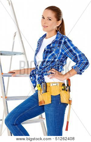 Confident happy DIY handy woman with a tool belt round her waist isolated on white