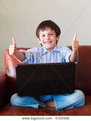 Niño jugando con su computadora portátil con los pulgares para arriba
