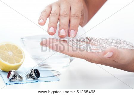 Woman's Hands Cleaning Jewellery With A Lemon