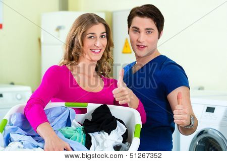 People in a launderette, washing their dirty laundry, in the background are washing machines