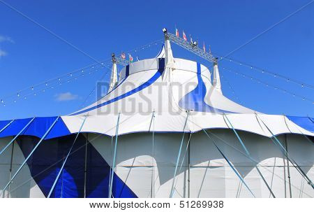 Blue and white big top circus tent with sky background.