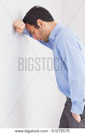 Worried man with fist clenched leaning his head against a wall