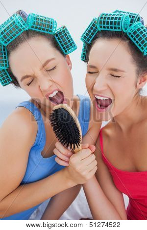 Friends in hair rollers holding hairbrush having fun and singing at sleepover
