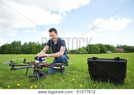 Young engineer crouching while fixing photography UAV in park
