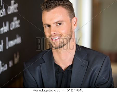 Portrait of young businessman next to menu board in coffeeshop