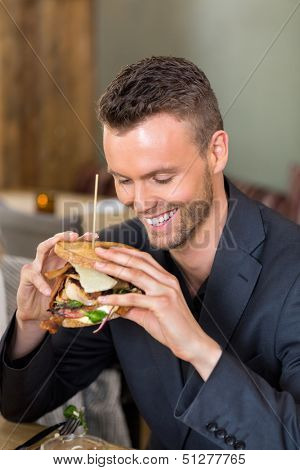 Happy young businessman holding large sandwich in coffeeshop