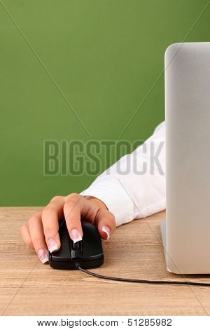 woman's hands pushing keys of pc mouse, on green background close-up