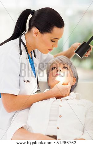 beautiful dermatologist inspecting middle aged patient's skin in office