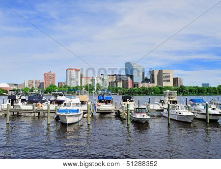 Boston Charles River with urban city skyline Hancock building and boats with blue sky.