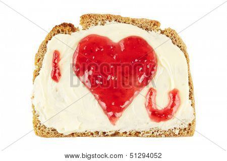Heart shape with a love message made of red jam on a slice of bread, isolated on white