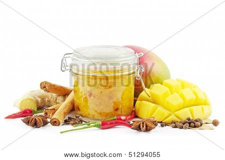 Homemade mango chutney in a glass jar with spices and mangoes