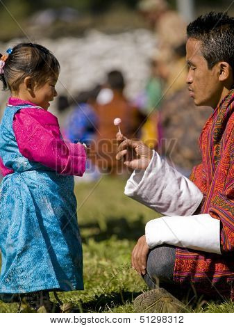 Jakar, Bhutan - October 24, 2010: Unidentified Girl Gets Candy From Her Father At The Jakar Tsechu O