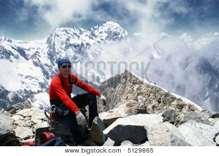 An alpinist sits on a top mountains