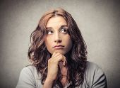 stock photo of cerebrum  - thoughtful woman looks up - JPG