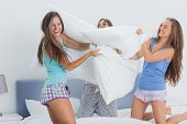 stock photo of slumber party  - Friends having pillow fight at home at slumber party - JPG