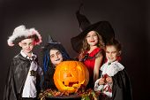 stock photo of traditional attire  - Cheerful children in halloween costumes posing with pumpkin - JPG