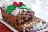 stock photo of custard  - Christmas fruit cake decorated with holly and berries - JPG
