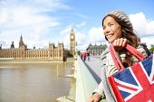 London woman holding shopping bag near Big Ben. Happy woman shopper smiling during travel vacation i