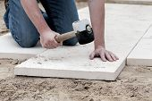 stock photo of bricklayer  - Installation of paving slabs with a huge hammer - JPG
