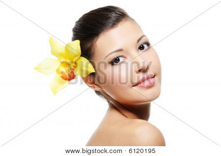 Smiling Female Face With Yellow Orchid From Her Ear