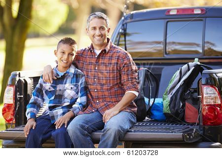 Father And Son Sitting In Pick Up Truck On Camping Holiday