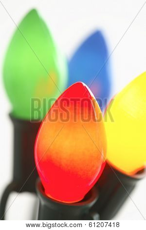 Multicolored Christmas light bulbs on white background