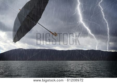 Flooded stormy landscape and flying umbrella in the air