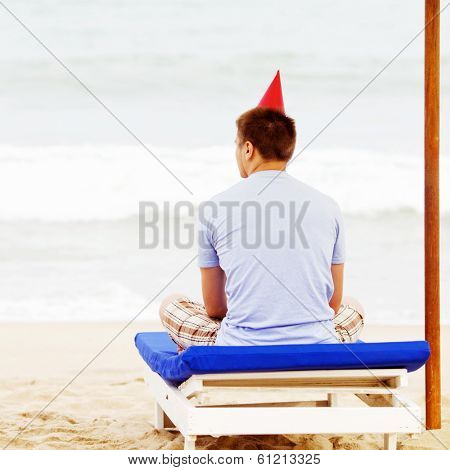 Young man in party hat sitting on beach bed under umbrella near sea