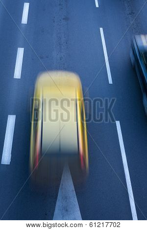 A blurred yellow car.