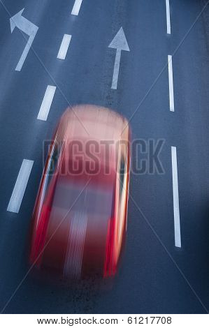 A blurred red car.