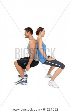 Side view of a fit young couple doing squats over white background