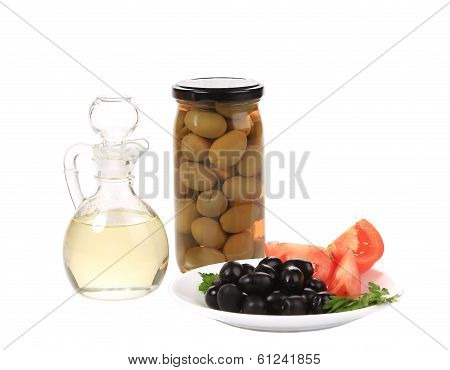 Bottle and bowl of olives with vinegar.