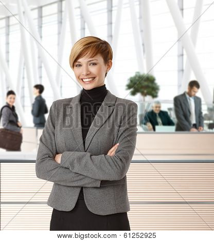 Attractive young happy businesswoman in office hallway.