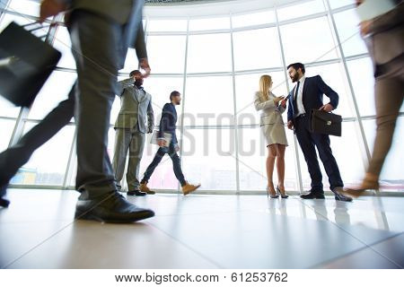 White collar workers communicating in office against window with their colleagues walking around