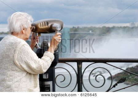 Senior Tourist Using Binoculars At Niagara Falls