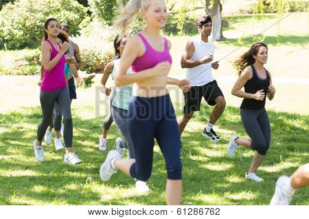 Group of athletes running on grassy land in park