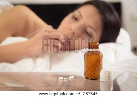 Woman In Bed About To Take A Tablet