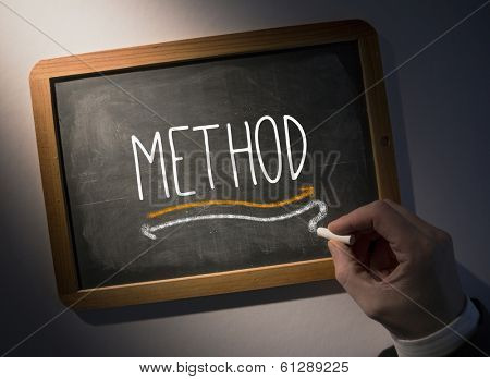 Hand writing the word method on black chalkboard