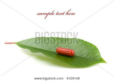 Red Pill Over A Green Leaf