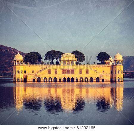 Vintage retro hipster style travel image of Rajasthan landmark - Jal Mahal (Water Palace) on Man Sagar Lake on sunset.  Jaipur, Rajasthan, India with grunge texture overlaid