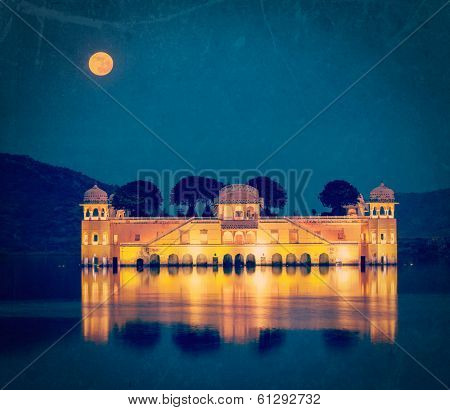 Vintage retro hipster style travel image of Rajasthan landmark - Jal Mahal (Water Palace) on Man Sagar Lake in the evening in twilight with grunge texture overlaid.  Jaipur, Rajasthan, India