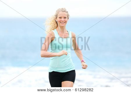 Running woman jogging outside on beach. Female fitness runner girl jogger training outdoors listening to music in earphones. Beautiful young blonde woman in her 20s.