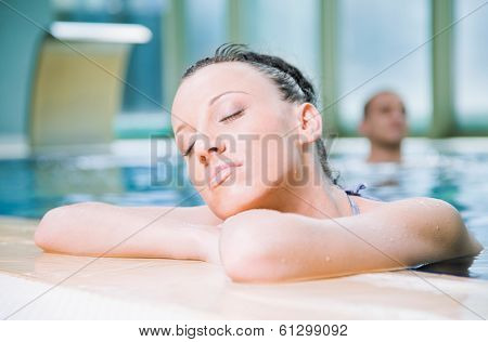 Young attractive female relaxing in a swimming pool