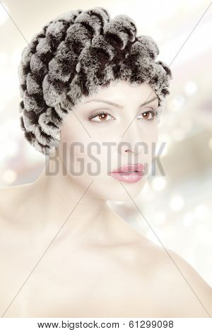 portrait of a beautiful young woman with fur hat isolated on white