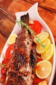 healthy lunch : whole fried sea sunfish on wooden table with lemons peppers and tomatoes and rosemar
