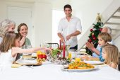 stock photo of christmas meal  - Happy multigeneration family enjoying Christmas meal at dining table - JPG