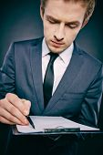 Portrait of a young businessman with document making notes