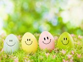 stock photo of cheers  - smiling easter eggs outdoor in green - JPG