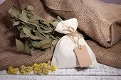 pic of sachets  - Textile sachet pouch with dried flowers on wooden table - JPG